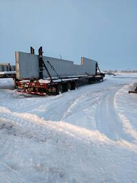 Drop deck expandable trailer with a 70' tall wall panel